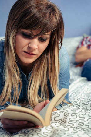 Young woman reading a book lying on the bed while her husband is resting