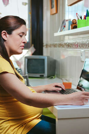 Pregnant woman with casual wear working from home with laptop
