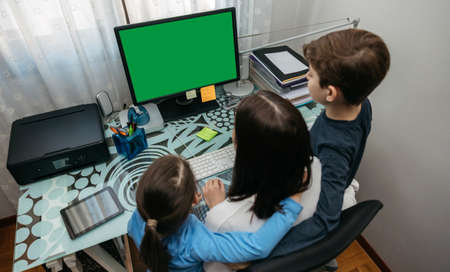 Top view of mother and children looking at computer screen at home Stock Photo
