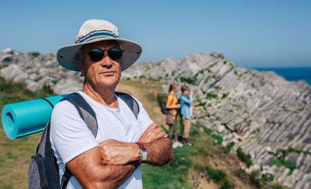 Senior man who practices trekking looking at camera