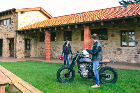 Young man waiting his girlfriend on custom motorcycle