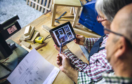Senior couple working in a carpentry workshop looking tablet with chair design