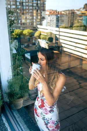 Young woman drinking coffee while watching the view through the window
