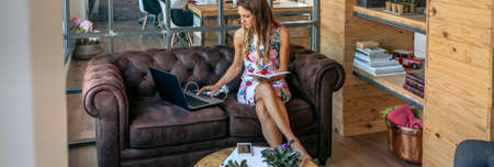 Businesswoman working with laptop sitting on the sofa in a coworking office