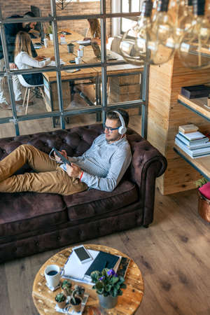 Young businessman lying on an office sofa with tablet and headphones