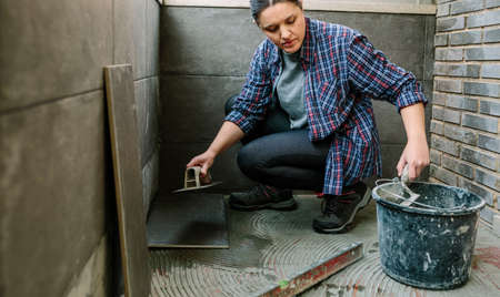 Female mason laying a new tile floor on a terrace Archivio Fotografico