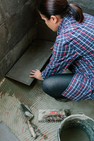 Unrecognizable female builder laying a new tile floor on a terrace