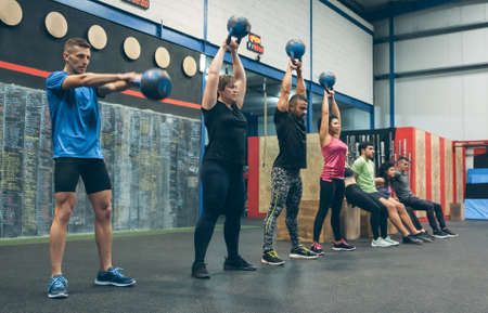 Group of athletes exercising with kettlebells and doing box squats Archivio Fotografico