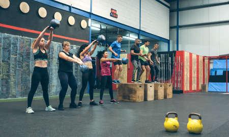 Sportswomen exercising with kettlebells and sportsmen doing box jumps