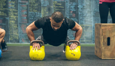 Sportsman doing push-ups with kettlebells in the gym Archivio Fotografico
