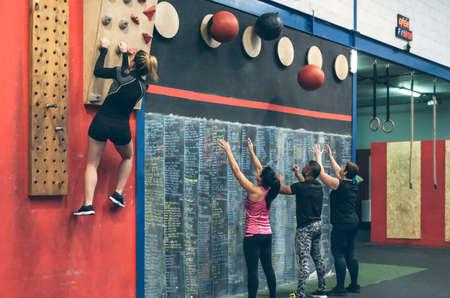 Group training doing wall ball and climbing wall at the box