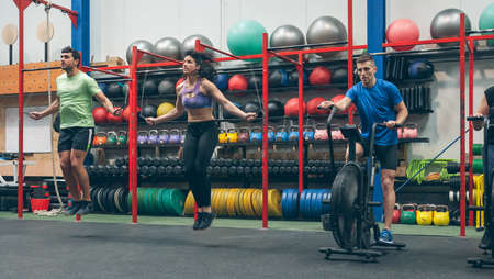 Group of athletes doing air bike and skipping rope at the gym Archivio Fotografico