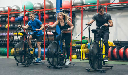Group of athletes doing air bike at the gym Archivio Fotografico