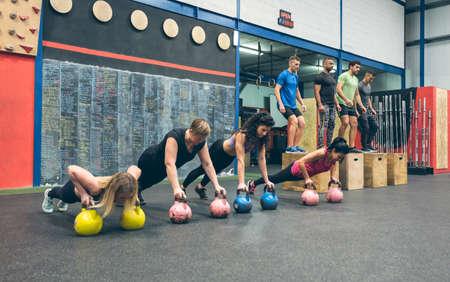 Sportswomen doing push-ups with kettlebells and sportsmen doing box jumps