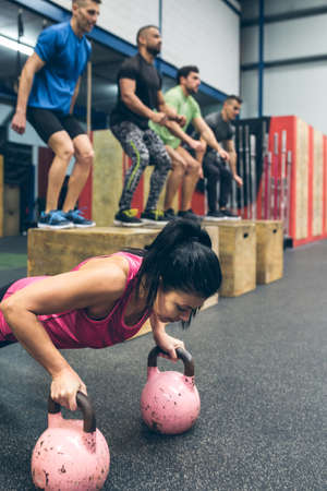 Sportswoman doing push-ups with kettlebells with mates doing box jumps in background Archivio Fotografico