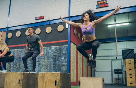 Group of athletes exercising jumping wooden box in the gym Archivio Fotografico