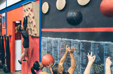 Sportswoman training hanging on the climbing wall at the gym and classmates doing wall ball