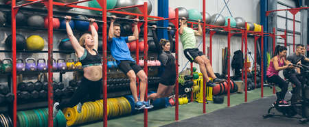 Group of athletes doing pull ups and air bike in the gym