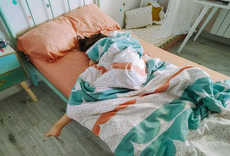 Unrecognizable little girl sleeping covered up in her bed Foto de archivo