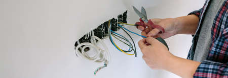 Unrecognizable female electrician working on the electrical installation of a house