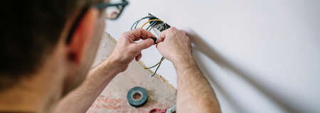 Unrecognizable male electrician wrapping cable with electrical tape on the electrical installation of a house