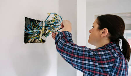 Female electrician working on the electrical installation of a house Standard-Bild