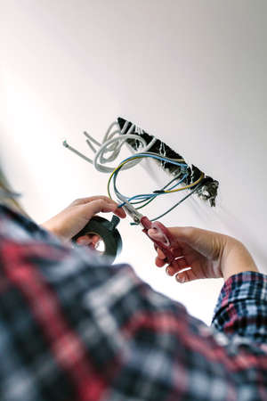 Unrecognizable female electrician cutting cables to the electrical installation of a house Archivio Fotografico