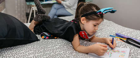 Little girl drawing in disguise while her mother teleworking in the bedroom