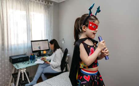 Little girl singing in disguise while her mother teleworking in the bedroom