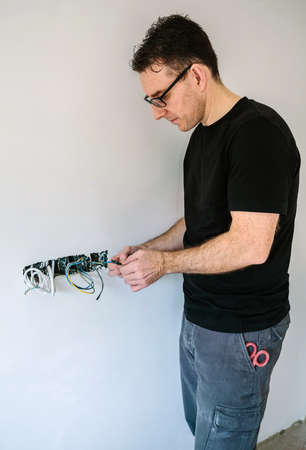 Male electrician wrapping cable with electrical tape on the electrical installation of a house Archivio Fotografico