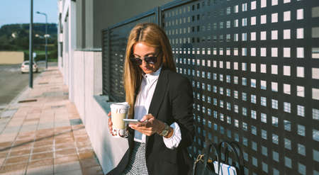 Businesswoman using mobile and drinking coffee sitting on a wall Archivio Fotografico