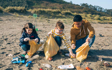 Group of young volunteers picking up trash on the beach Archivio Fotografico