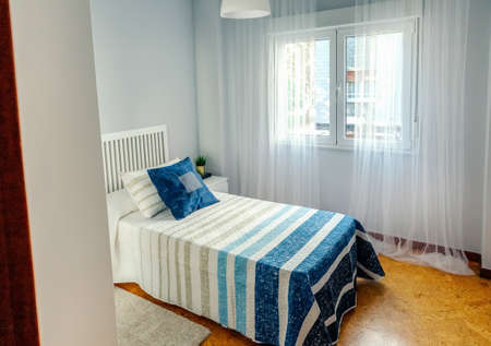 Interior of cozy single bedroom decorated with quilt and curtains
