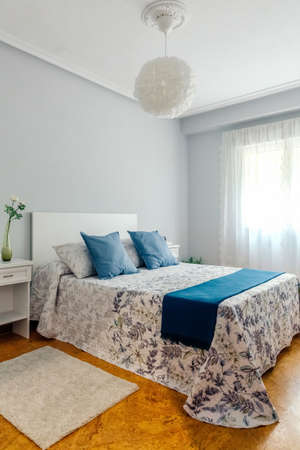 Interior of cozy double bedroom decorated with quilt and curtains