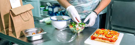 Unrecognizable cook in restaurant kitchen preparing takeaway orders
