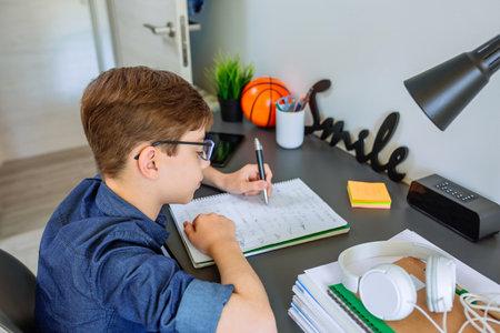Left handed teenager doing homework on desk in his bedroom
