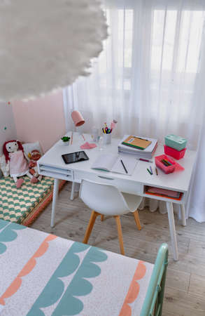 Top view of desk in girls bedroom decorated in pastel colors