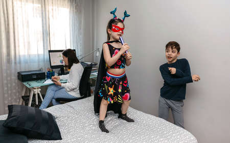 Children playing and dancing on the bed while their mother works in pajamas at home. Conciliation family work concept Standard-Bild