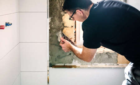 Male mason leveling cement with a trowel to tile the wall