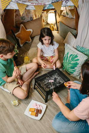 Family preparing smores with small barbecue at home