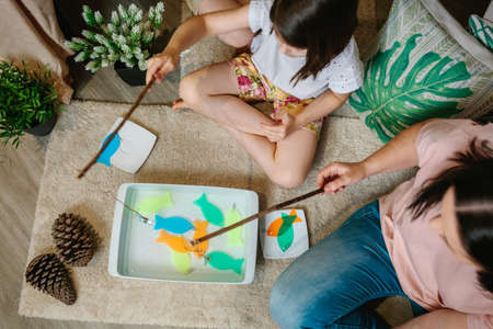 Top view of unrecognizable mother and daughter camping at home playing diy fishing game