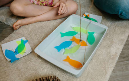 Homemade fishing game made with sticks, magnets and acetate