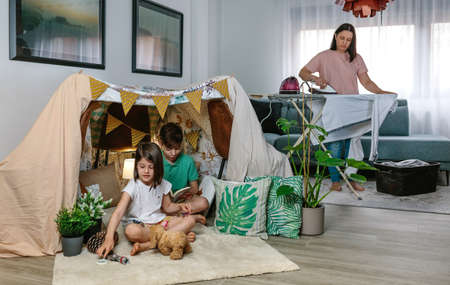 Mother ironing while her children play camping at home in the living room