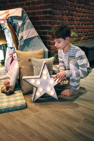 Male teen placing a star lamp helping preparing a slumber party Foto de archivo
