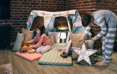 Male teenager helping little sister prepare a diy tent for pajama party Foto de archivo