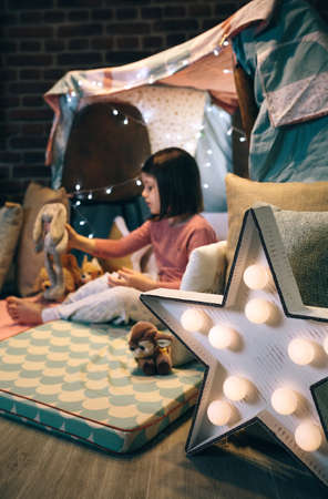 Star lamp craft made with cardboard and pin pong balls with girl playing in a teepee in the background. Selective focus on star lamp in foreground Foto de archivo