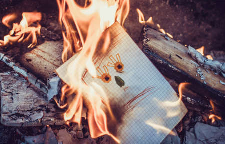 Paper sheet on fire. Flaming paper sheet. Burning paper.