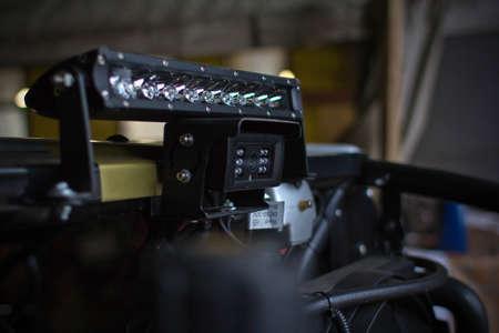 leds: Headlights of black ATV quadbike isolated on city pavement, close up Stock Photo