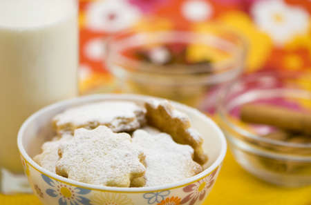 Homemade cookies with a glass of milk and different spices in the background. photo