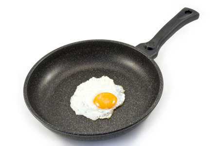 Egg in a frying pan isolated on white background photo